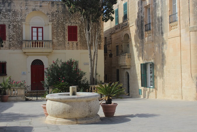 Square in Mdina surrounded by honey colored buildings with red and blue doors