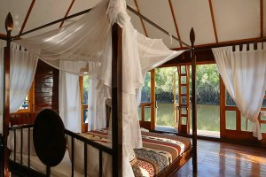 Our four-poster bed in our flaoting river lodge, Mandina Lodges, The Gambia by travel photographer, Kathryn Burrington