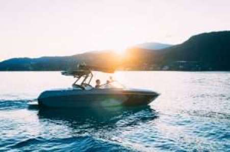 Bowrider boat with kneeboard on water at sunset