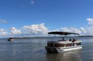 Tropical 2450 Performance Pontoon on the water, available with Coastal Ventures Boat Hire