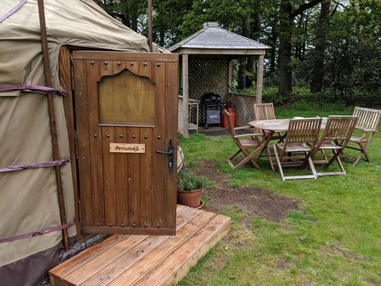 woodn door of yurt and bbq in background