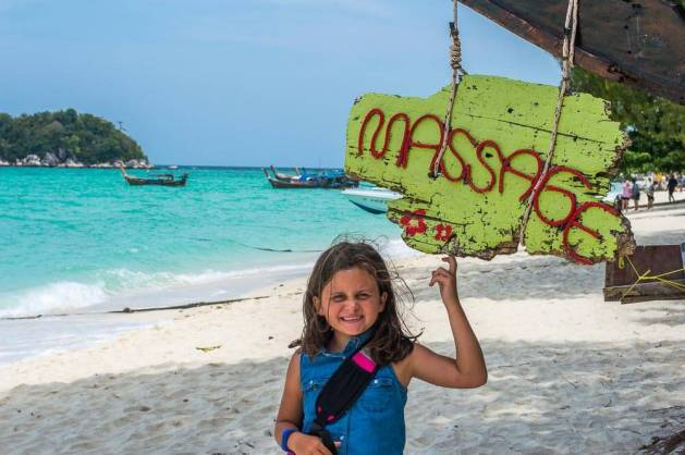 Child on beach by sign