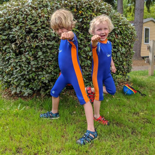 two boys by hedge in wetsuits
