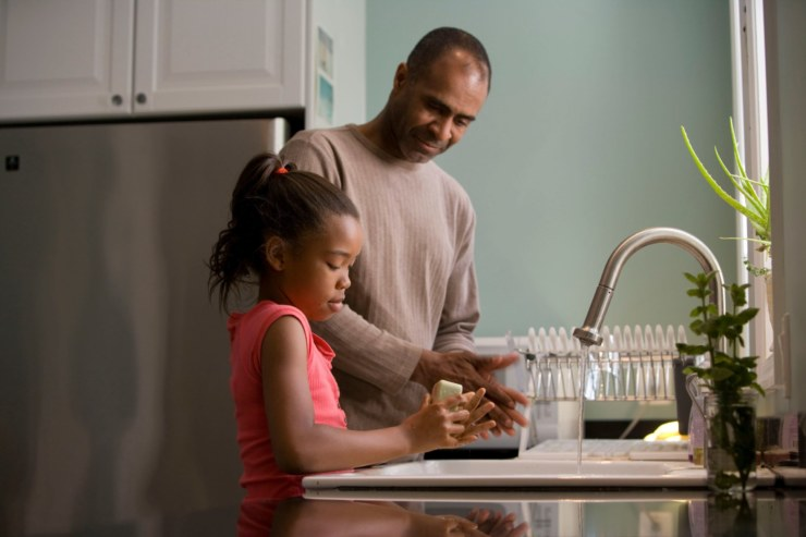 Man and daughter washing their hands