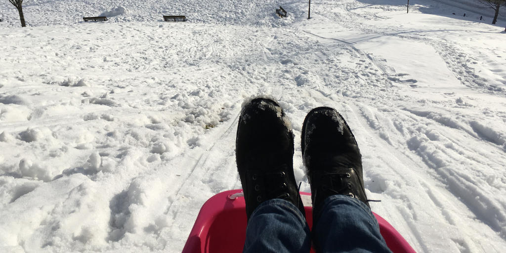 feet at the top of a sledding hill