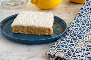 an icing topped lemon square on a blue plate