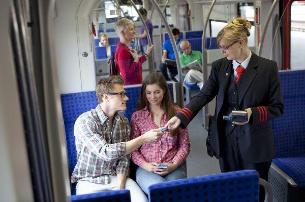 Schaffner und Fahrgäste im Zug.