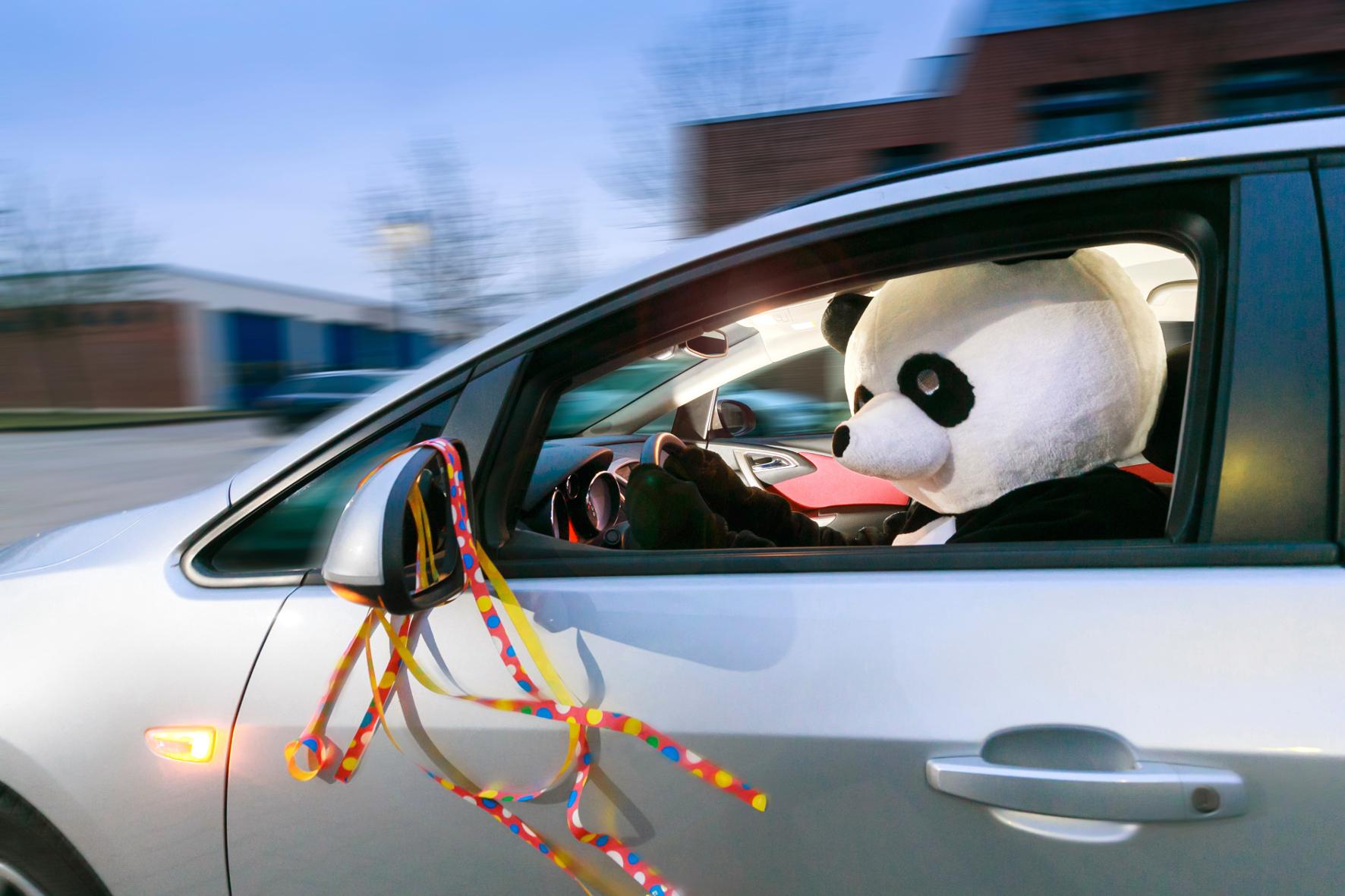 Maskiert im Karneval mit dem Auto unterwegs