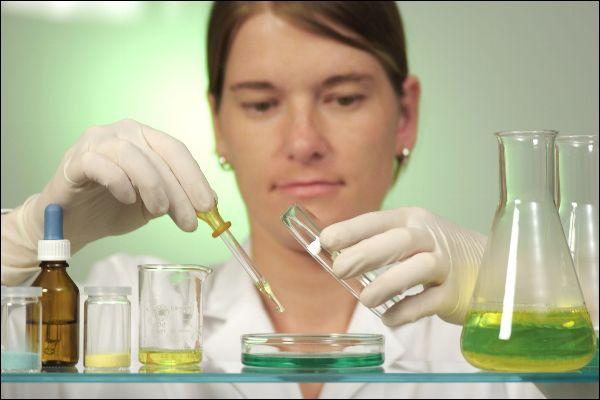 Frau im Labor hält Reagenzglas in der Hand.