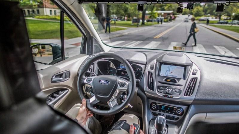 Im Innenraum eines Autos richtet sich der Blick auf eine Person die einen Zebrastreifen überquert.