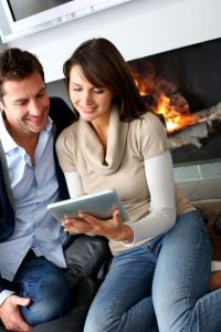15832034 - couple sitting by fireplace and websurfing with tablet