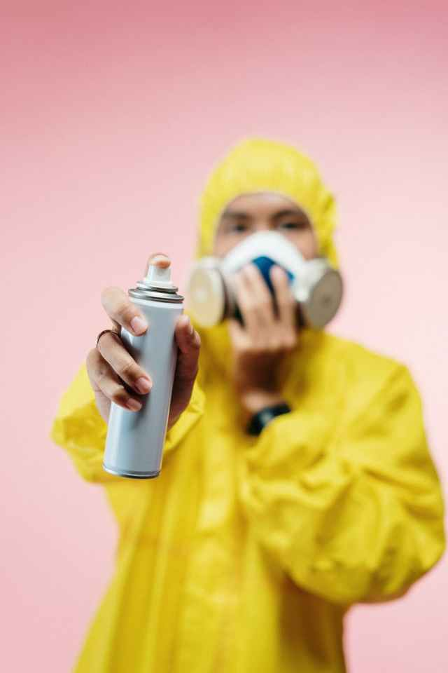person in yellow protection suit holding a spray can