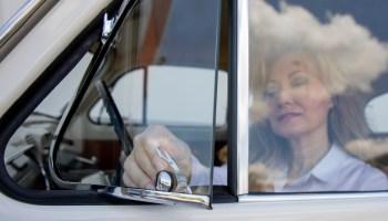 Frau als Fahrerin öffnet Dreiecksfenster in altem Auto.