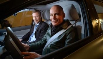 Zwei Männer in einem roten Auto blicken durch die Scheibe der Fahrertür.