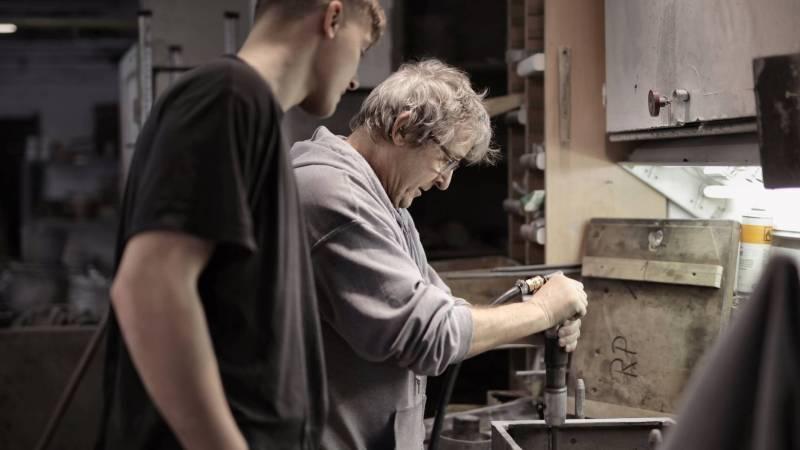 Vater und Sohn in der Werkstatt bei der Arbeit.