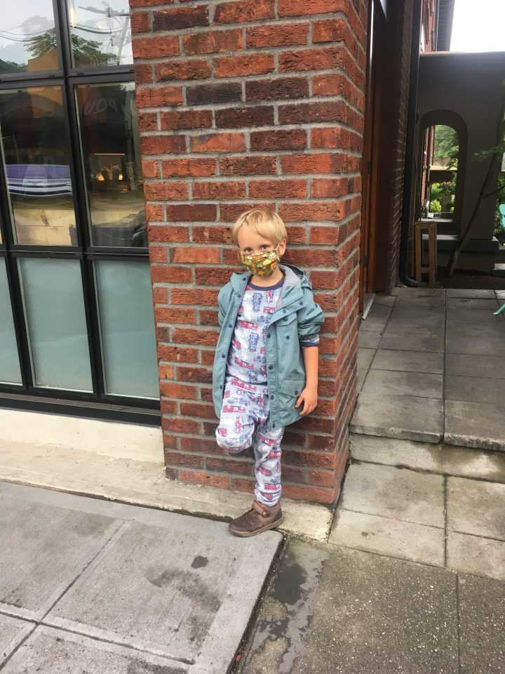 Child standing in front of a brick building wall with a mask on