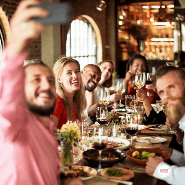 people eating dinner out at restaurant for Over 100 Ways to Save Money