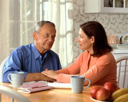 Senior man and family member having discussion at table