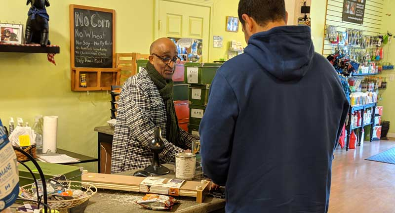 Tré Bone owner, Serge Ouattara, helping a customer at Tré Bone Pet Supply in Portland.