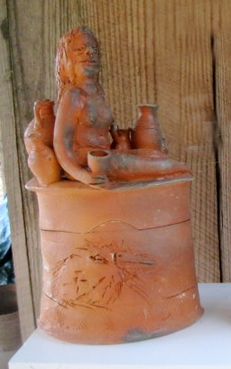 A lidded container with nude woman and pots.
