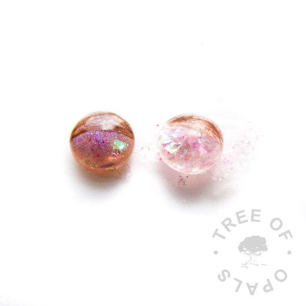 Why Do You Make Extra Cabochons? lock of hair proof image, an example where a client asked for pink sparkles. The left is pink shimmer powder with a little pink opalescent and the right is pink opalescent and pink hexagonal glitter Tree of Opals lock of hair blanks