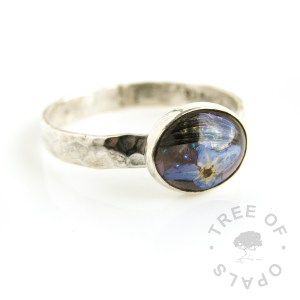 solid sterling silver 3mm textured flower ring with lock of hair and opalescent flakes cast in a 10x8mm resin cabochon in a rubover silver bezel setting, handmade from scratch by silversmith and memorial artist Nic Kamminga with hair and forget me not