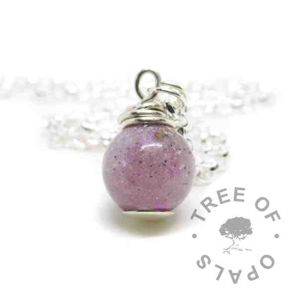 cremation ashes orb. Cremains with orchid purple resin sparkle mix, no birthstone. Set with solid sterling handmade headpin and shown with a medium classic chain necklace upgrade. Watermarked copyright image by Tree of Opals