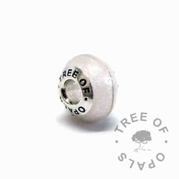unicorn white breastmilk bead with brunette first curl. Tree of Opals core