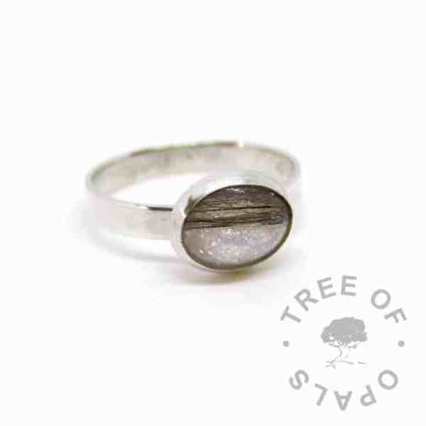 silver breastmilk ring, 10x8mm setting with dark hair and breastmilk, unicorn white resin sparkle mix. 3mm brushed band, 935 anti-tarnish silver