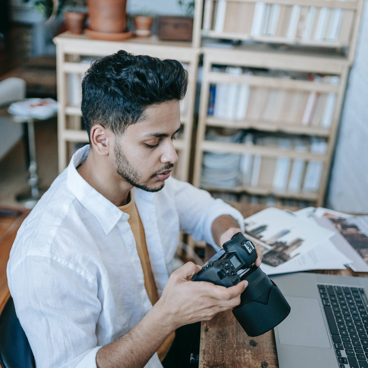 pensive ethnic man photographer sitting with photo camera at table at home