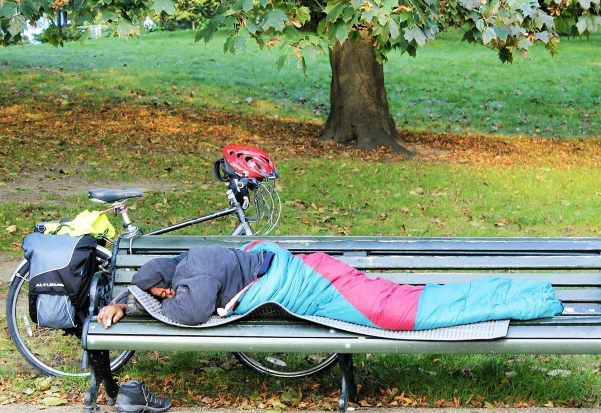A homeless man trying to sleep on a Park bench in Cornwall.
