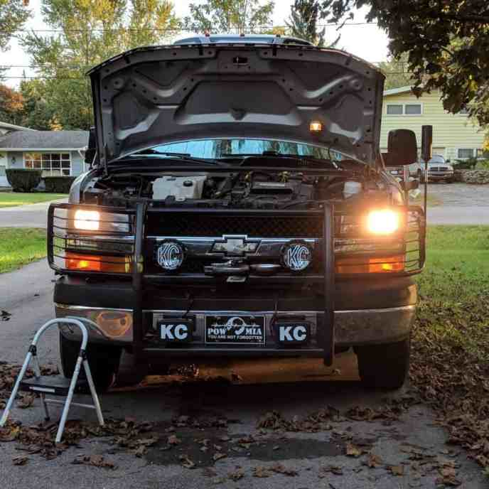 Chevy Express van with headlights on