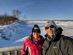 man and woman on beach overlook in winter