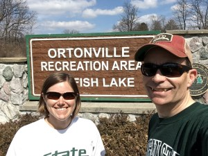 woman and man in front of state park sign