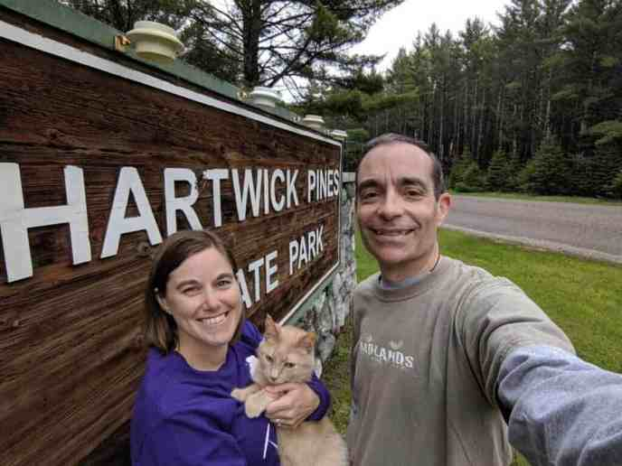 man and woman at Hartwick Pines State Park sign