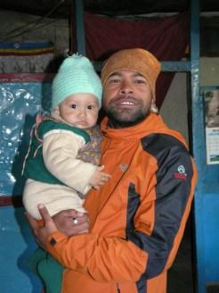 Sudip sosteniendo a un bebe en Mustang