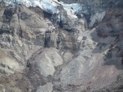 The glacier had blown out a pocket of mud. The area to the center right of the photo is a stream of reddish mud that is flowing out from under the glacier. As I watched I could see large boulders coming down and it sounded like a jet plan noise.
