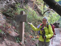 Lori plays Vanna at the mileage sign at the start of the Eagle Creek trail.