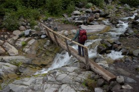 Lori making her way over the log bridge on Falls Creek heading to Comet Falls.
