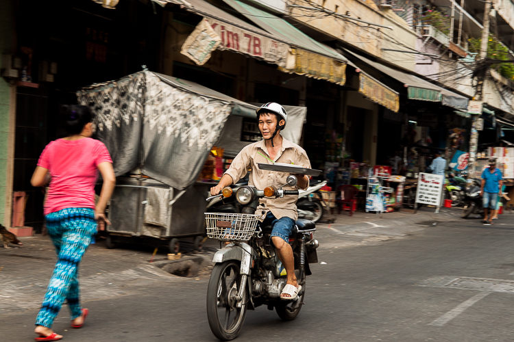 A man on a motorbike balances a tray while whizzing by