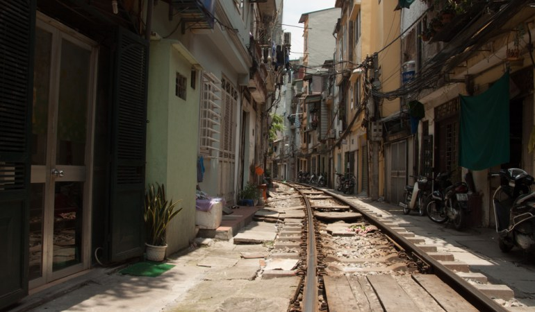 The narrow tracks pass in between the buildings