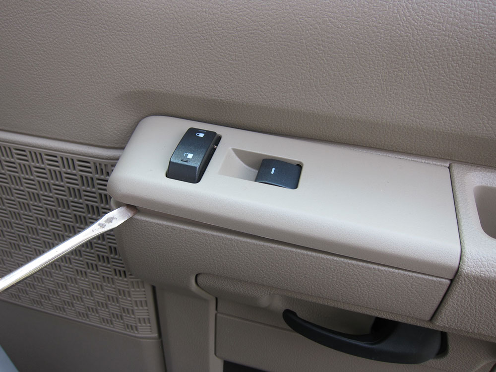 To access the last screw, pry up the panel with the window controls.