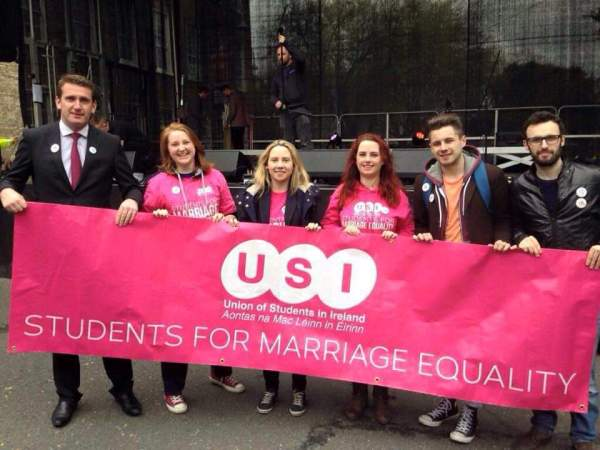 "Former USI president, Laura Harmon, standing with five other people and holding a banner that reads, ""Students for Marriage Equality"""