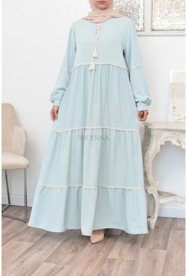 Longue robe bohème avec détails de broderies et pompons femme voilée.