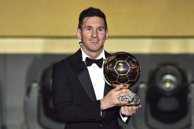 Messi posing with football trophy