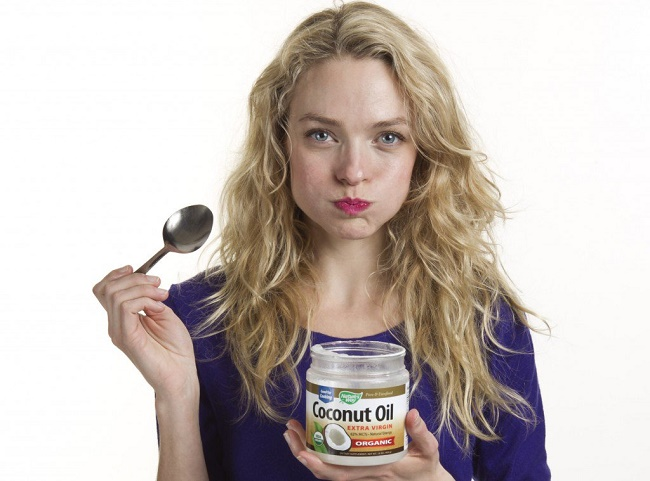 girl eating coconut oil to cure Yeast Infection