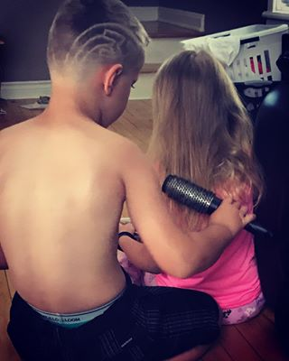 brother cleaning sister's hair