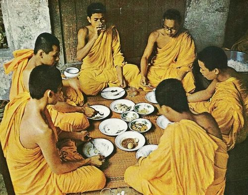 buddhist monk eating by sitting on floor