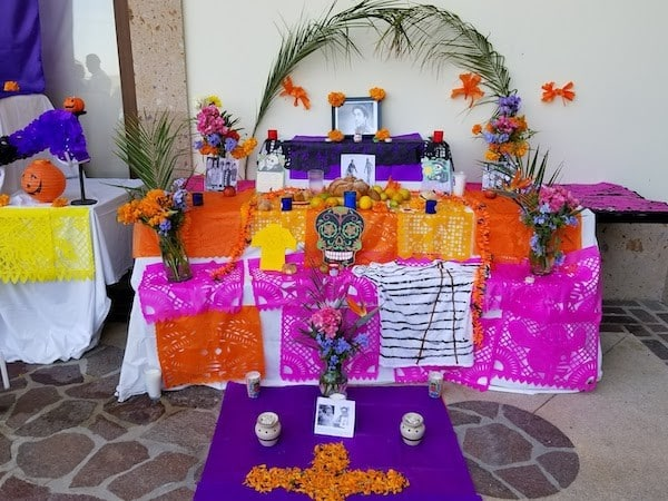 Día Los Muertos Ofrenda with food, colorful flowers and a photograph of a loved one at Pueblo Bonito Pacifica
