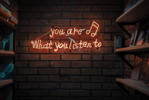 A neon sign with the words 'You are what you listen to'